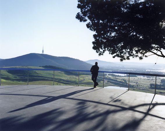 A man leans on a railing at the Arboretum looking at a view which includes Black Mountain in the distance