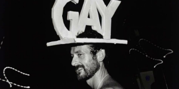 Man wearing hat with letters that spell 'gay'