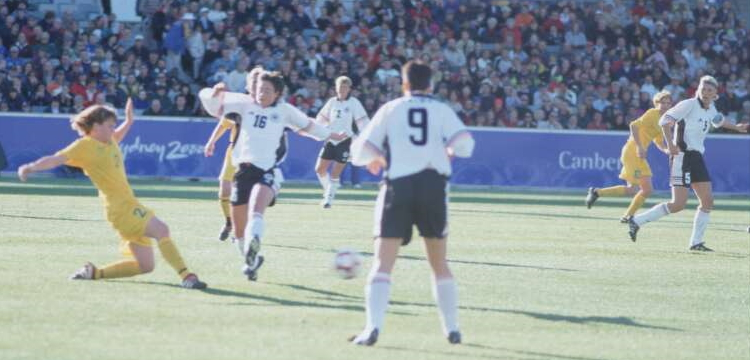 7 women soccer players on a field with a ball at the 2000 Olympic games