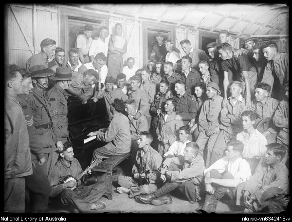 Australian and foreign soldiers surrounding a soldier playing the piano, New South Wales, ca. 1918