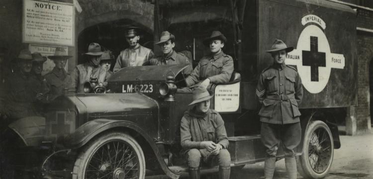 Nine soldiers gathered around an ambulance