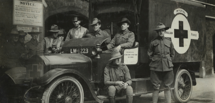 Nine soldiers gathered around an ambulance