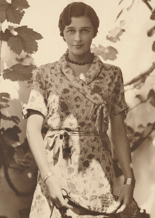 Woman standing in the sunshine in front of a tree, wearing a patterned dress and finger wave hairstyle