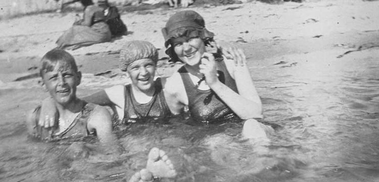 Three young people sitting in shallow water at Brighton Beach, Melbourne, Victoria, ca. 1925