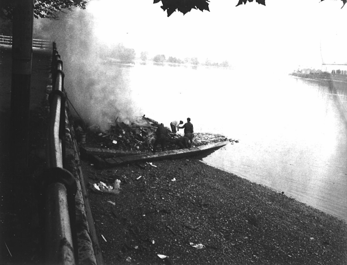 Black and white photograph of burned boat on bank of the Thames River