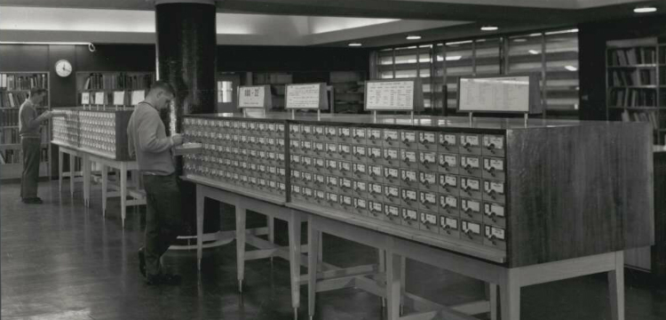 Two men browsing the card catalogue at Baillieu Library