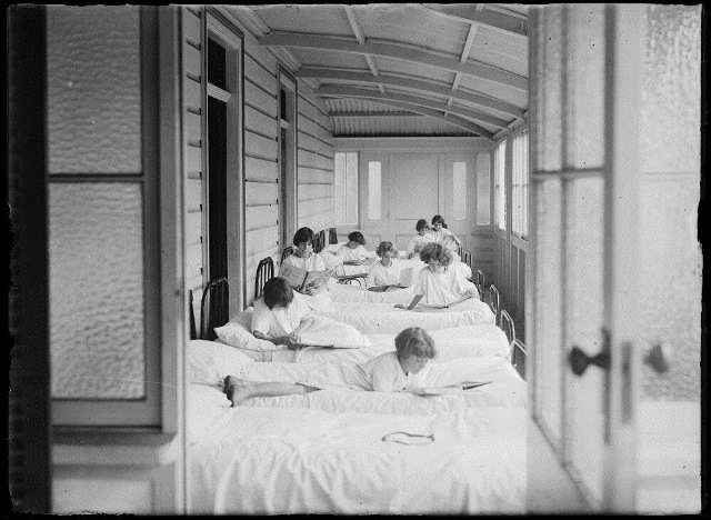 Eight girls reading on a line of beds