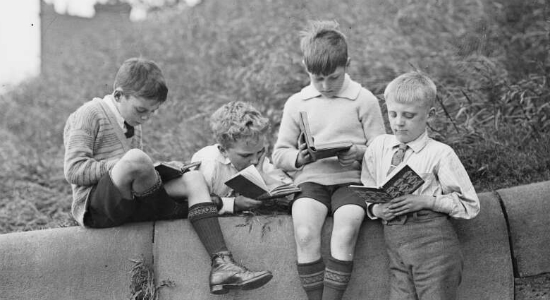 Four boys sitting on brick wall reading books