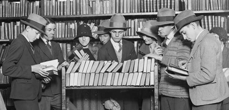 people standing around a trolley full of books in a library
