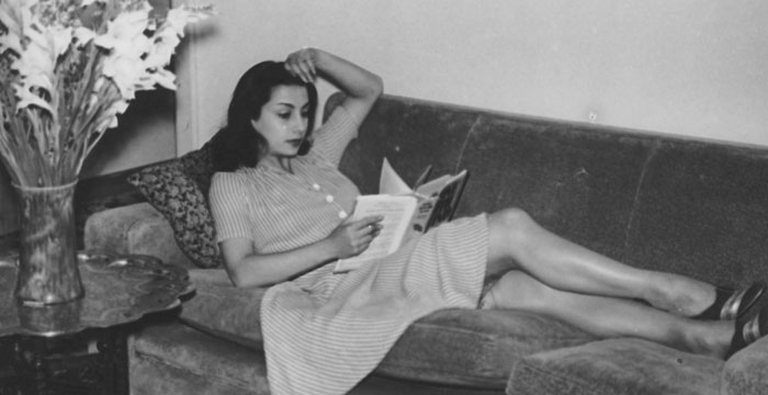 Girl lying on couch reading