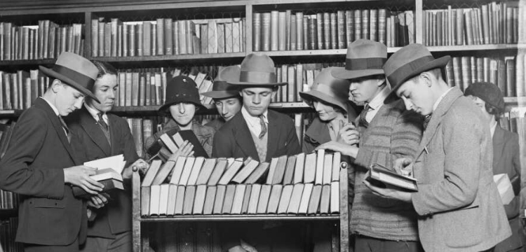 Nine people gathered around trolley of books in a library
