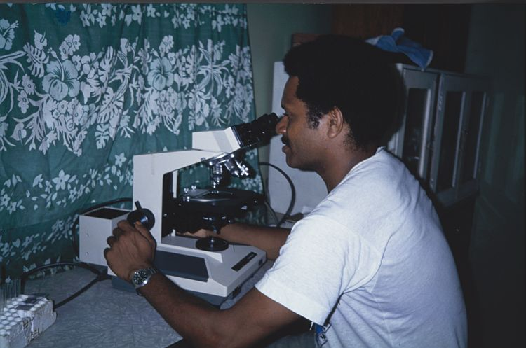 Photograph of a New Guinean medical staff member looking through a microscope