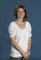 Dr Lucy Fraser in the NLa studio in fron o a blue background. Lucy is wearing a white top