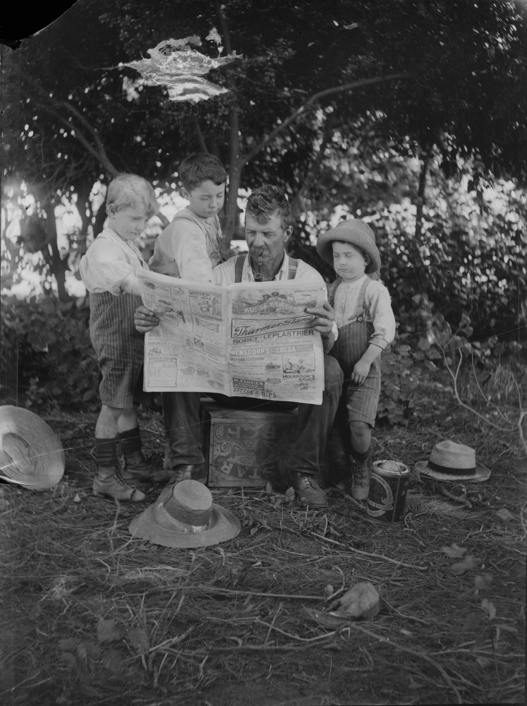 Picture of man and boys reading a newspaper
