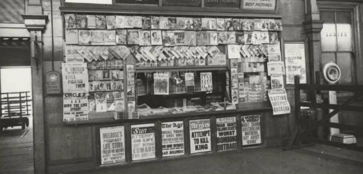 "Newspaper stand in a railway station showing newspapers with headline ""Attempt to kill King"""