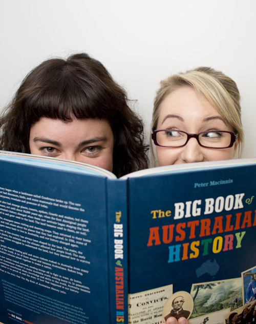 Kate and Jemma peer over the top of the new book