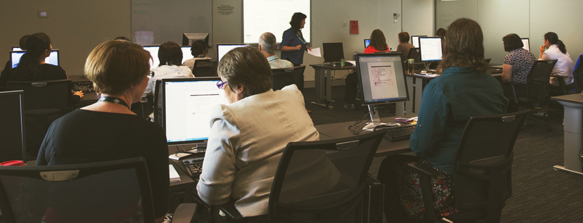 Photograph taken at training. Trainees are sitting at computer terminals.