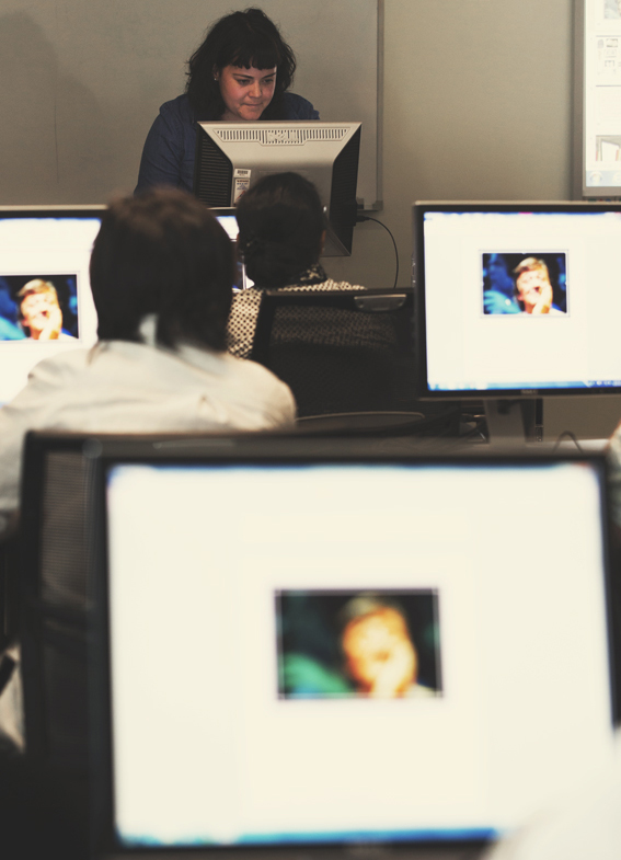 Photograph of Kate Ross training staff. Image of Stephen Fry can be seen on the computer screens.