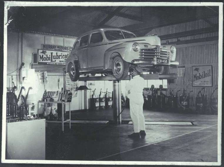 Mechanic working on the undercarriage of a motor car