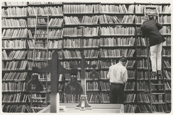 B&W photograph of boys studying shelves of books