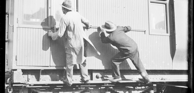 Two men trying to open the door of a goods train, New South Wales, ca. 1930