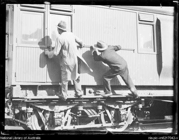 Two men trying to open the door of a goods train, New South Wales, ca. 1930 [picture].