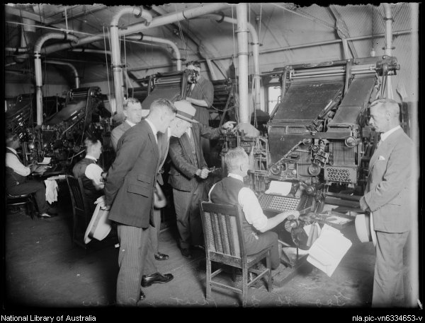 Man sitting at typesetting machine with others watching over him