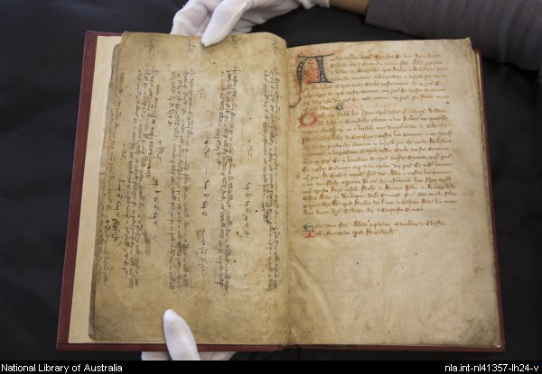 Hands holding medieval cartulary