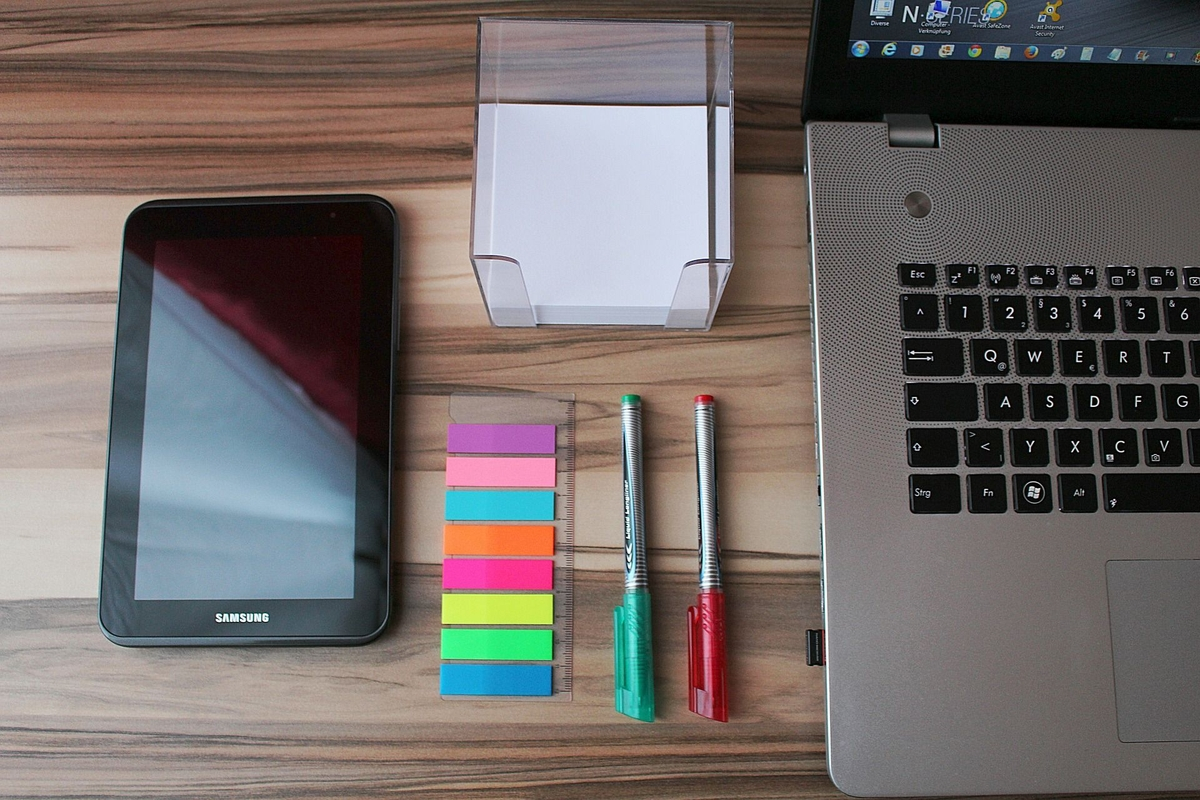 Samsung tablet, pens, paper, sticky notes and laptop neatly organised on a desk
