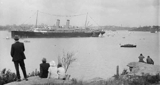 People watching as a steam ship with bunting sails through the harbour, Sydney, ca. 1920s