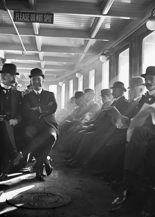 Men wearing bowler hats sitting on a ferry going to work