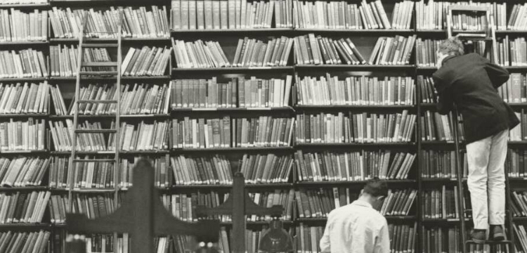 Two men browsing bookshelves