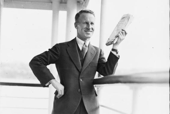 Sir Charles Kingsford Smith holding a newspaper on the deck of a ship, New South
