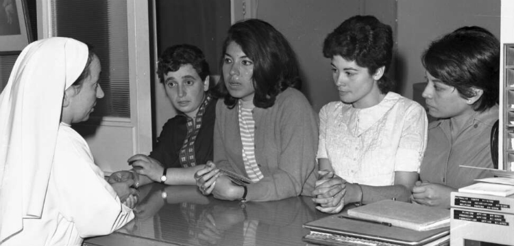 Social worker Sister Margherita speaking to four young South American migrant women over a counter at the Catholic Family Welfare Bureau in Sydney
