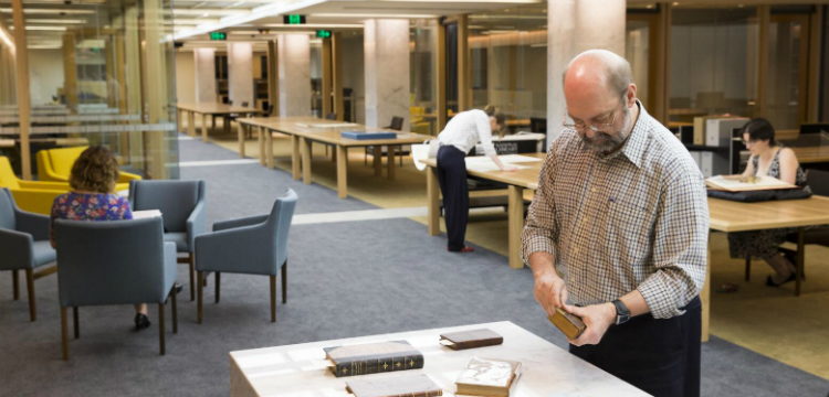 Man holding book at desk in Special Collections Reading Room