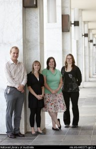 Four summer scholars leaning on marbel pillar on NLA podium