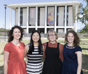 Four summer scholars standing on lawn in front of NLA, Gretel, Talisha, Meg and Morgan