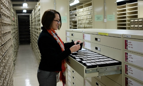 Tessa at the AJCP cabinets in the stacks