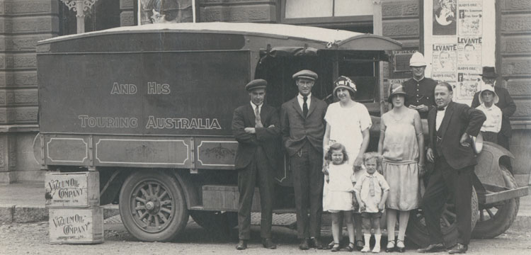Picture of family group standing next to a car