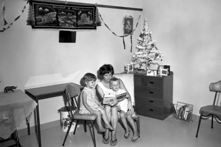 A woman reading to two children in a room with Christmas decorations at the Villawood Migrant Hostel, New South Wales, 17 December 1968