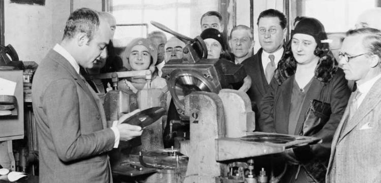 Mischa Levitzki and crowd of people standing around a vinyl record machine inspecting a vinyl record