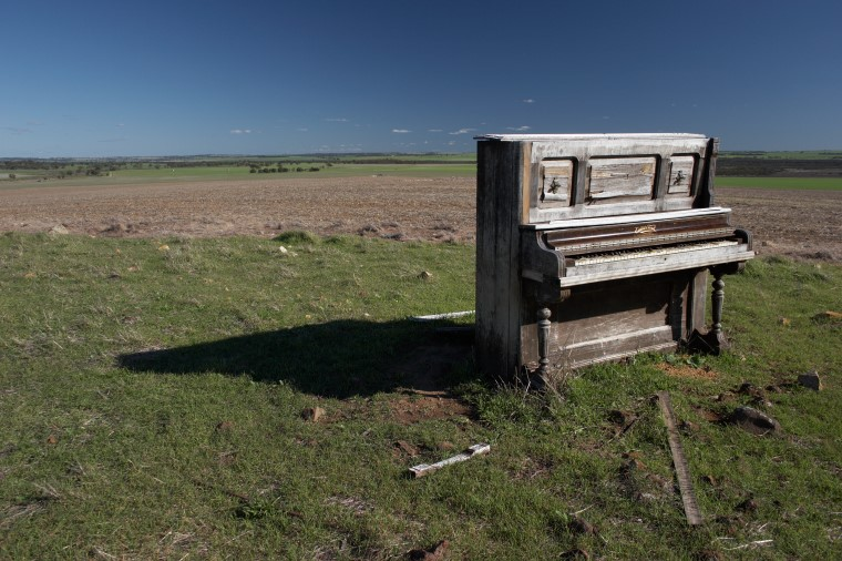 Ruined piano in open grassland