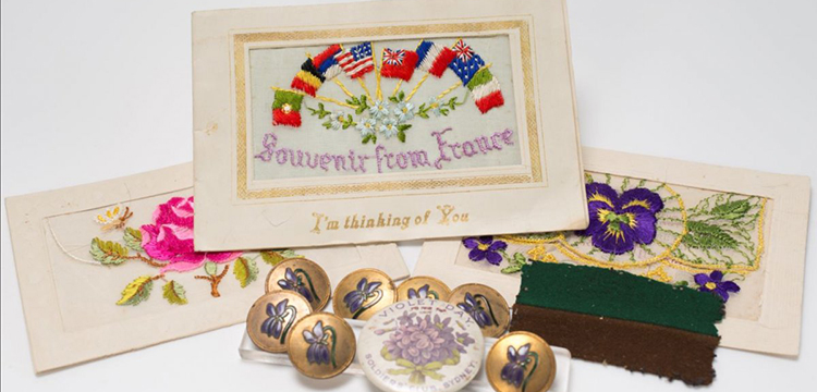 Various First World War souvenirs from the Library's collection including embroidered silk post cards and Violet Day badges