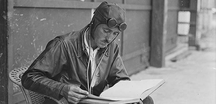Fairfax Media (circa 1929). Aviator Captain Leggatt sitting in a chair reading a logbook, New South Wales. nla.pic-vn000006256158