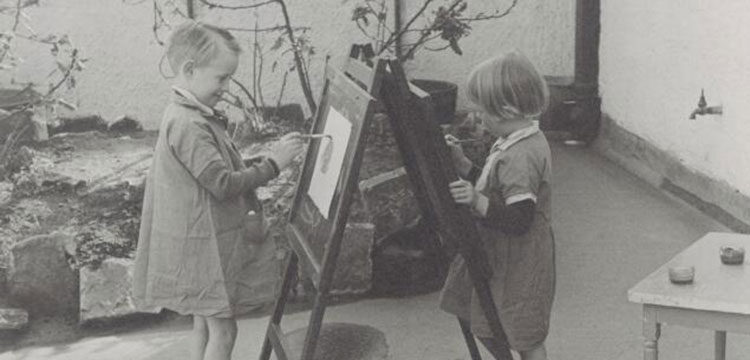 Two children painting on a easel