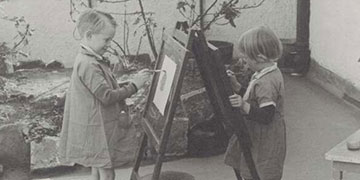 Two children painting on an easel