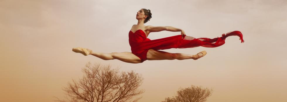 Girl in red leaping in desert landscape