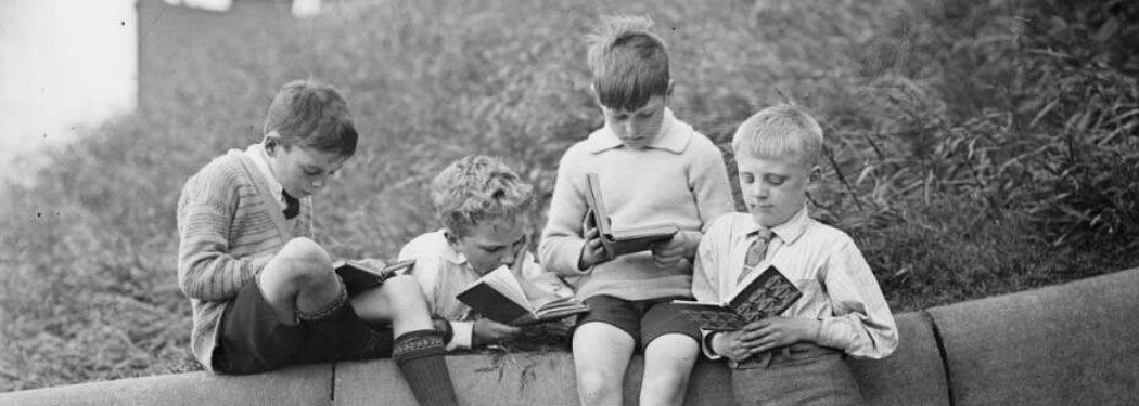 3 schoolboys reading books on a wall