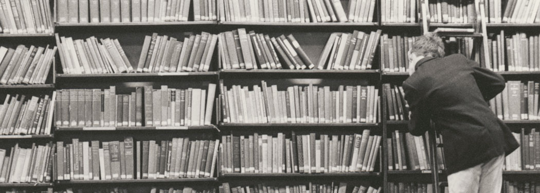 A man on a ladder looking through bookshelves