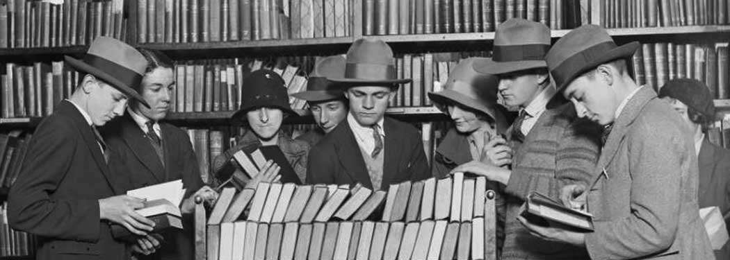 People looking through a trolley full of books at a library